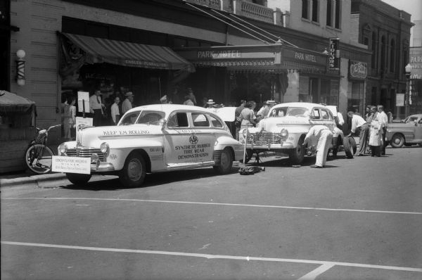 "Men doing a periodic rotation of the synthetic and recapped tires on one of the two cars parked in front of the Park Hotel and participating in the American Automobile Association (AAA), the 25,000 mile ""Keep 'Em Rolling"" tire safety tour."
