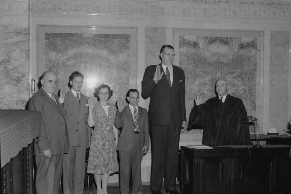 "Clifford Thompson, the second tallest man in the world, being sworn into the Wisconsin state bar at the Wisconsin State Capitol by Justice Elmer E. Barlow.  Others from left to right: Francis Sweitlik, dean of the Marquette Law School, Robert Schoen, Jane O'Meila, James D""Amato, and Clifford Thompson.  All were students at the Marquette Law School in Milwaukee."