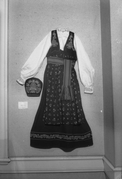"Norwegian dress and hat displayed as part of an exhibit of Elaine Smedal's ""Norwegian Wisconsin as a Source of Design."" Elaine Smedal arranged the exhibit as part of her Masters thesis. The collection was displayed at the Memorial Union."