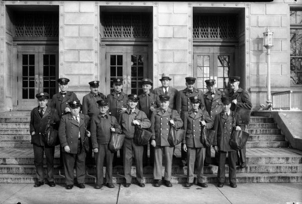 Fifteen Madison U.S. Mail carriers standing on the front steps of the Madison U.S. Post Office. Lower row left to right: Martin T. Digney, Thomas M. Carey, G. Nicholas Mueller, George Flad, Raymond M. Nienaber, Paul W. Kroseman, and Michael Cawley. Upper row left to right: Raymond M. Tierney, Walter S. Fauerbach, Bernhard F. Pahlmeyer, John T. Behrend, Joseph Wirka, Louis F. Nelson, Henry L. Olsen, and Nels E. Anderson.