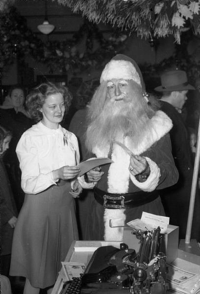 Woman buying a war bond from Santa Claus, who was helping other Manchester employees wait on crowds of purchasers at the bonds-only sale on the store's main floor. Santa Claus is really Fred Claus who lives above the St. Nicholas Cafe, 120 West Main Street.
