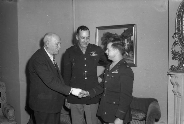 War hero Capt. Richard I. Bong, of Poplar, Wisconsin, credited with knocking out 21 Japanese planes in the South Pacific, shaking hands with Governor Walter Goodland at the Governor's Residence. Looking on is Brig. Gen. S.W. FitzGerald, commanding officer of Truax Field.