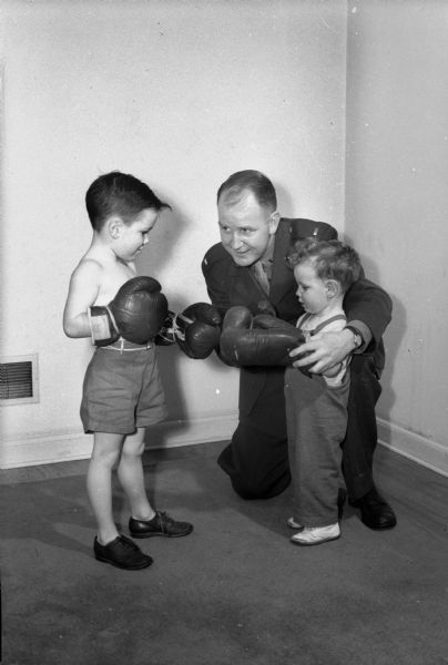 Lieut. John Walsh, University of Wisconsin boxing coach who was in the marine corps in Okinawa, teaching his two sons Johnny and David to box.