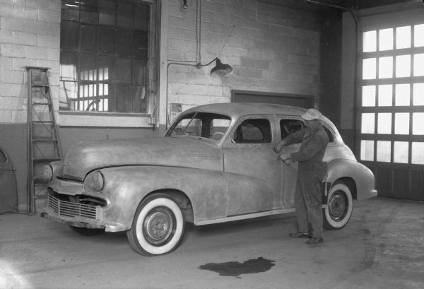 In the recently completed paint department of Royal Body Co., 9-13 N. Brooks Street, a worker is preparing a sedan, the body and fenders of which are going to be re-painted after being damaged in a fire.