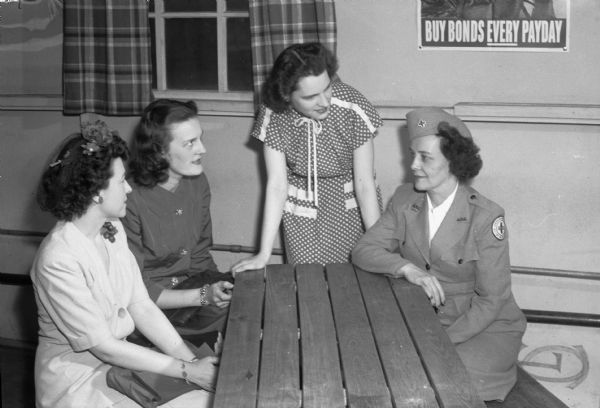 "Group portrait of three members of ""Parlor Tricks"" being instructed by Mrs. Frances Maloney, Red Cross recreation director.  Pictured left to right: Lorraine Jones, 130 East Gorham Street; Helen Lunde, 2140 University Avenue; Mary MacLennan, 711 East Johnson Street; and Mrs. Maloney. The ""Parlor Tricks"" are a group of young women volunteers who entertain convalescent patients at the Army Air Force regional hosptial at Truax Field."