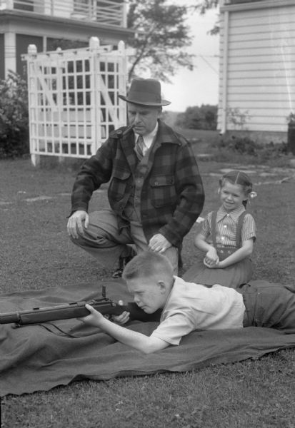 Ira Kurth, 3918 Manitou Way, with children Stuart and Kathleen. Stuart is aiming a gun while his father and sister look on.