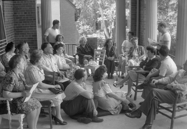 "Group of men and women listening to a speaker at the Abraham Lincoln School, Summer Institute. The Abraham Lincoln School for Social Science of Chicago, Illinois, sponsored a Summer Institute in Madison for several summers, including 1945.  The students who attended the two week sessions were mostly adult union workers and their families.  They lived in rooming houses on Langdon Street and Lake Lawn Place, attended lectures and participated in recreational activities.  The photographs show the teachers with groups of students, both indoors and out-of-doors, the students participating in recreational activities such as boating and badminton, and the children with a day care worker. The School was run by former University of Wisconsin Associate Professor of Classics Alban D. Winspear.  Their textbook was called ""Why Work for Nothing"", espousing Marx's theory of value.  The school had a communist / leftist philosophy and was often confused with the University of Wisconsin's School for Workers."