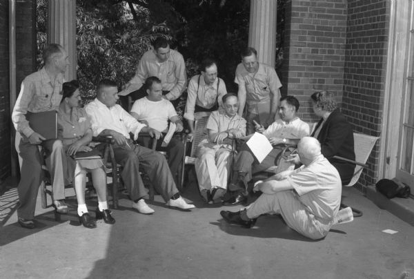 "Group of students listening to a lecture on a porch. The Abraham Lincoln School for Social Science of Chicago, Illinois, sponsored a Summer Institute in Madison for several summers, including 1945. The students who attended the two week sessions were mostly adult union workers and their families. They lived in rooming houses on Langdon Street and Lake Lawn Place, attended lectures and participated in recreational activities. The photographs show the teachers with groups of students, both indoors and out-of-doors, the students participating in recreational activities such as boating and badminton and the children with a day care worker. The School was run by former University of Wisconsin Associate Professor of Classics Alban D. Winspear. Their textbook was called ""Why Work for Nothing"" espousing Marx's theory of value. The school had a communist / leftist philosophy and was often confused with the University of Wisconsin's School for Workers."