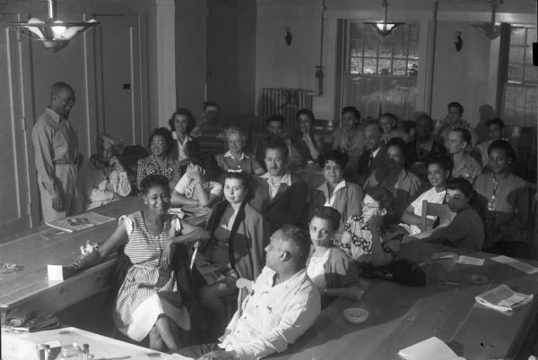 "Students attending a lecture. The Abraham Lincoln School for Social Science, Chicago, Illinois, sponsored a Summer Institute in Madison for several summers, including 1945. The students who attended the two week sessions were mostly adult union workers and their families. They lived in rooming houses on Langdon Street and Lake Lawn Place, attended lectures and participated in recreational activities. The photographs show the teachers with groups of students, both indoors and out-of-doors, the students participating in recreational activities such as boating and badminton and the children with a day care worker. The School was run by former University of Wisconsin Associate Professor of Classics Alban D. Winspear. Their textbook was called ""Why Work for Nothing"" espousing Marx's theory of value.  The school had a communist / leftist philosophy and was often confused with the University of Wisconsin's School for Workers."