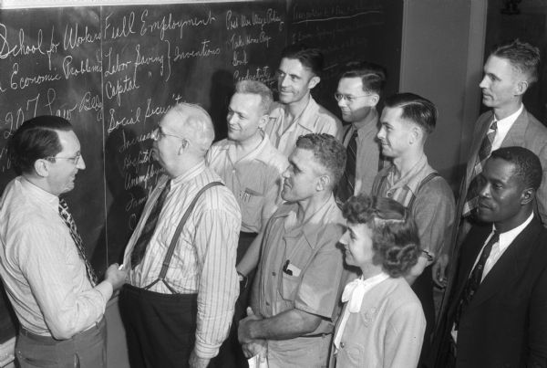 University of Wisconsin School for Workers, group of students and teacher standing, looking at bulletin board with list of classes/topics.  In 1945 the University of Wisconsin School for Workers conducted three institutes: a general institute, an institute for AFSCME members and an industrial relations institute for church leadership.