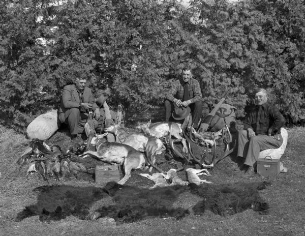 Stoeber hunting party. Three men are posed with assorted game.