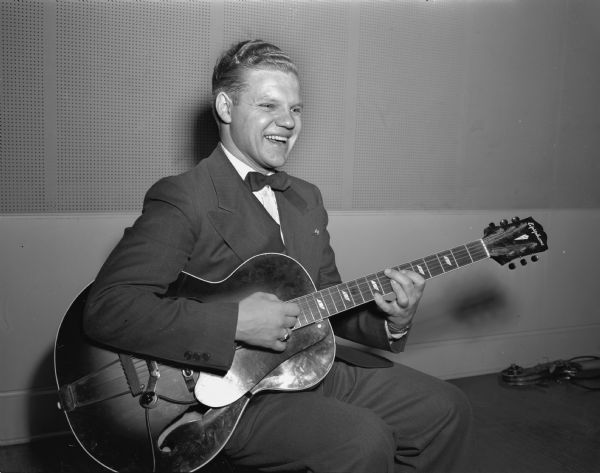 Portrait of Jimmie McCloskey with his guitar in the WIBA studio, 110 East Main Street.