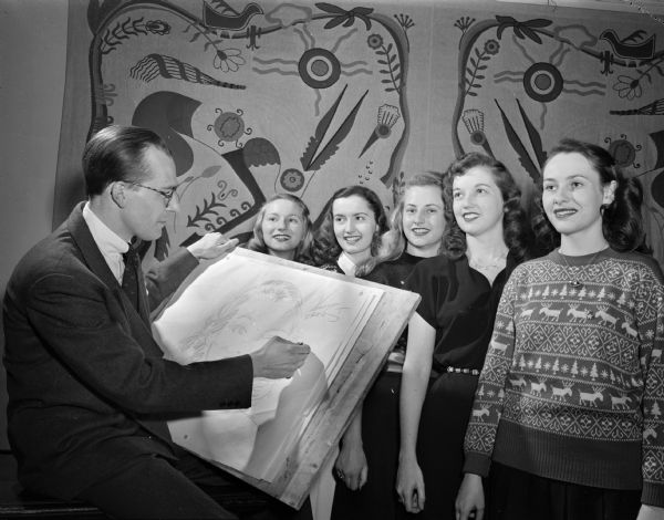 "Cartoonist Ken Ernst and five University of Wisconsin  Badger Beauties, one of whom he will select to be cast as one of the characters in his ""Mary Worth"" comic strip.  The woman are, left to right:  Virginia Freund; Alberta Baxter; Bette Lami; Marilyn Moevs; and Ruth Schmitt."