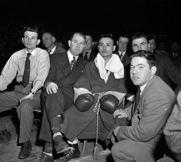 Four University of Wisconsin boxing principals watching a bout at the NCAA National Boxing Tournament at the University of Wisconsin-Madison Field House. From left are John Brandes, a Second; John J. Walsh, Coach; boxer, Dick Miyagwa; and Morrie Holzman, Manager.
