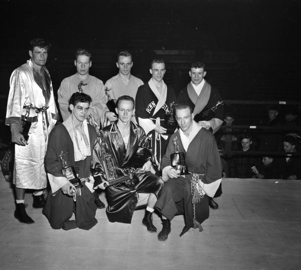 The eight NCAA National Boxing Champions with their trophies. The tournament was held at the University of Wisconsin-Madison Field House. Back row, left to right are: Art Saey, Miami; Laune Erichson, Idaho; Herb Carlson, Idaho; Glen Hawthorne, Penn State; and Gerald Auclair, Syracuse. Front row, left to right are John Lendenski, Wisconsin; Charles Davey, Michigan State; and Cliff Lutz, Wisconsin.