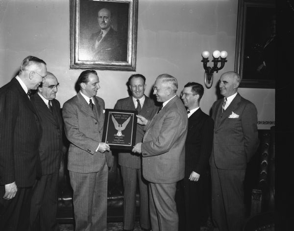 Harry Porter, Jr., representing the National Safety Council, Chicago, presenting a plaque to Governor Rennebohm in recognition of an outstanding state traffic safety record. Also present at the ceremony are, from left, James R. Law, chairman of the state highway commission; Ben L. Marcus, commissioner of the motor vehicle department; Porter; Fred G. Bishop, first assistant state superintendent of public instruction; Governor Rennebohm; Prof. Leonard Hillis, University of Wisconsin, extension division; and R.C. Salisbury, director of the safety division of the motor vehicle department.