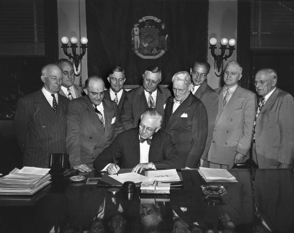 Governor Oscar Rennebohm signing a bill with Voyta J. Wrabetz, Commissioner of the Industrial Commission, and others looking on.
