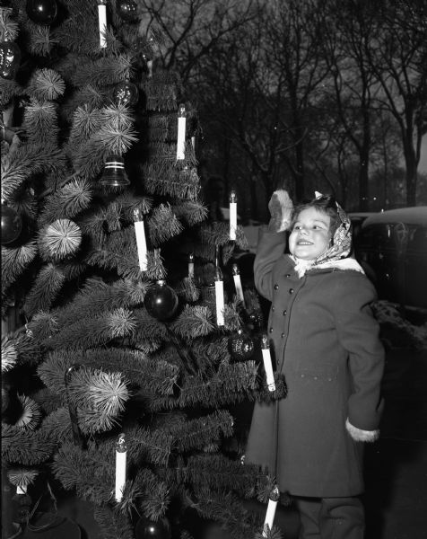 Natalie Schwartz, 137 Talmadge Street, admiring a Christmas tree outdoors.