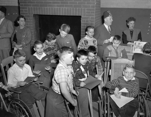 Floyd Ferrill leads a group of handicapped children in a Christmas carol at the Madison Shriners yule party at the Washington Orthopedic School, 545 West Dayton Street.
