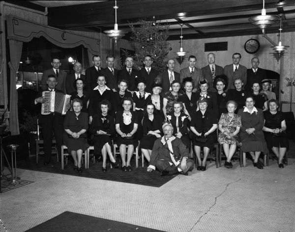 Group portrait of men and women at the Madison Dye Works party.  Included in the portrait on the left is an accordion player. One man sitting on the floor in the front is wearing a Santa Suit.