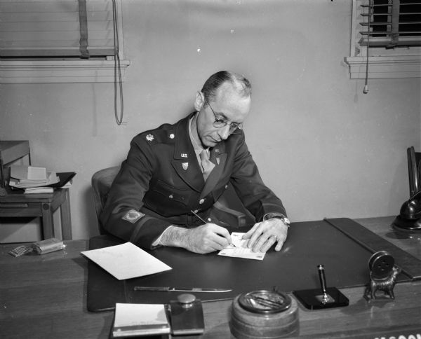 Major Glenn McConagha, commandant of the United States Armed Forces Institute (USAFI) seated at a desk signing a course completion certificate. USAFI provides college level course work to servicemen-students. Seventy colleges and universities are cooperating with USAFI in providing materials and offering credit. USAFI is headquartered at 102 North Hamilton Street.