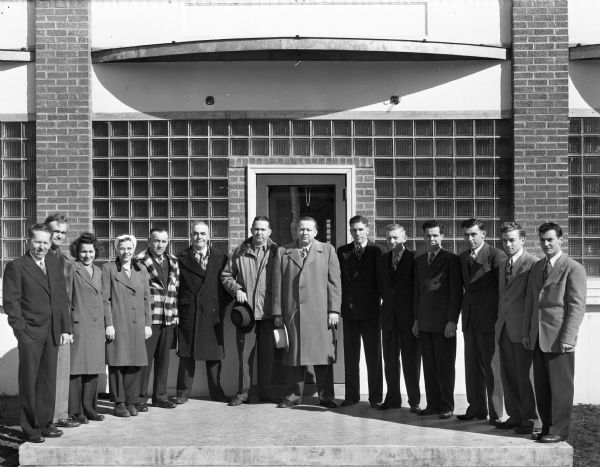 Group portrait of fourteen employees standing at the front door of the Regal Products, Ltd. at Gays Mills. E. Tex Reddick is the company president.