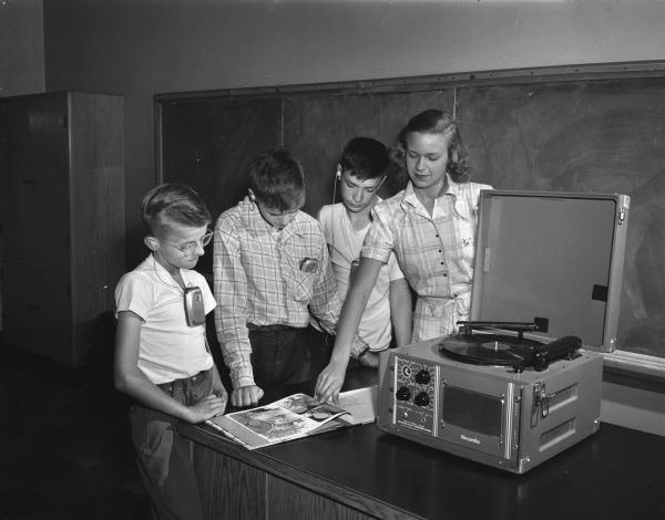 Participants in a large-scale hearing clinic held at Washington School in Madison and sponsored by the University of Wisconsin departments of speech and education with the cooperation of the state bureau for handicapped children. Marion Olejniczak, Milwaukee, is shown playing a phonograph record with related pictures in books with three children.