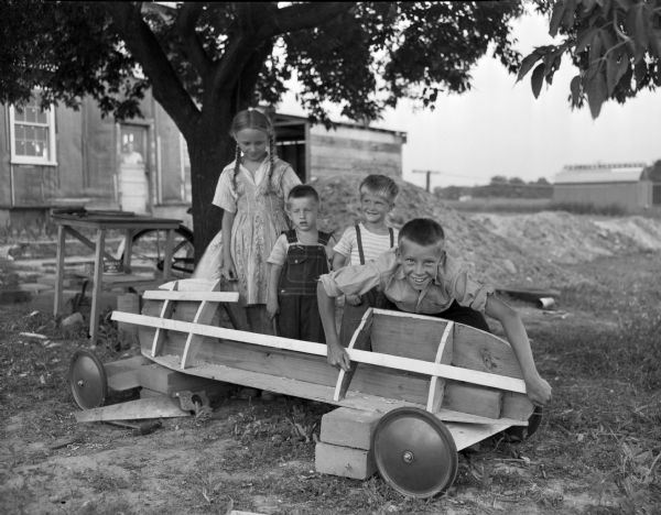 Jimmy Christiansen is shown posing with the body of his derby car while three friends observe. Left to right: Florence Brown, John Brown, Gary Sachs, and Jimmy Christiansen, who will compete in the Soap Box Derby.