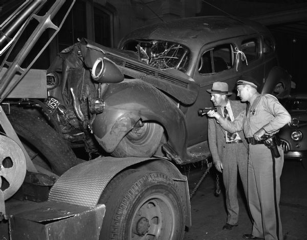 Crashed automobile on tow truck, with traffic officer, Russell Klitzman, and deputy sheriff, Eldon Johnson, viewing the car.
