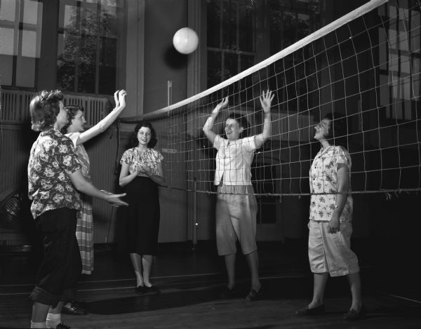 Members of the YWCA's Teen and Twenty club playing volleyball. Shirley Taubert, 2515 Kendall Avenue, center, is keeping score. Players are, left to right: Phyllis Bryant, Route 3, Mary Kruel, 143 North Hancock Street, Iris O'Connell, 2034 Rusk Street, and Rosalie Kerl, 2514 Chamberlain Avenue.