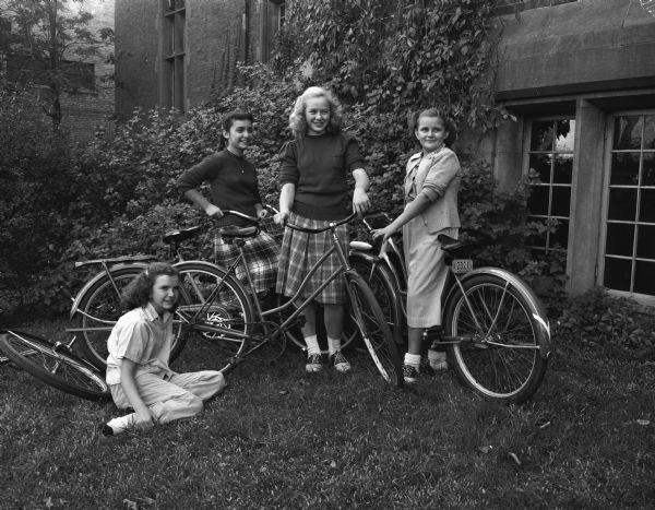 "Four members of the Junior Y Teen group with their bicycles prior to starting out on a ""bicycle hike"" and picnic. Shown left to right: Charlotte McVicar, 724 Conklin Place; Mae Wein, 525 West Johnson Street; Donna Feggestad, 213 North Mills Street; and Betty Black, 712 West Dayton Street."