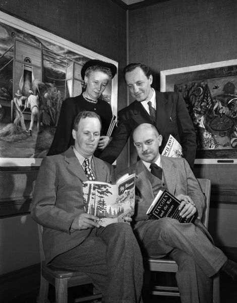 Four Madison authors are shown together holding books they have written. Seated are Francis F. Bowman and Prof. William Hesseltine.  Standing are Miss Emilie Weidenbeck and Raymon Coffman. Behind them on the wall hang two paintings.