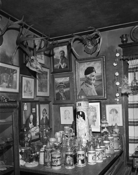 House interior showing a collection of pictures, beer mugs, and deer antlers.