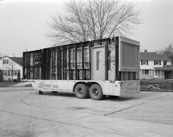 Truck carrying Lustron house sections  to be assembled on a building site.