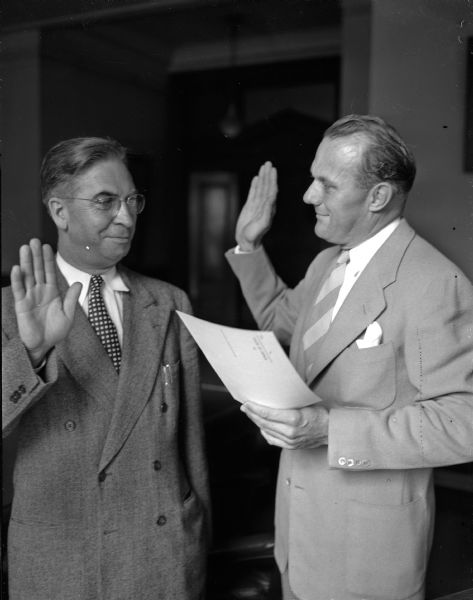 George E. Watson, Wauwatosa, at left, being sworn in as the new State Superintendent of Public Instruction, by Robert C. Zimmerman, Assistant Secretary of State, at right.