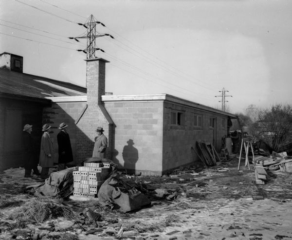 Four members of the Madison Curling Club inspect their new clubhouse at Burr Jones Field on East Washington Avenue. Pictured are Dr. Ralph E. Campbell, Laurie Carlson, Walter Rhodes, and William Reese.