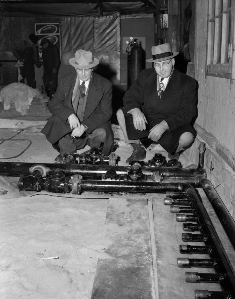Two members of the Madison Curling Club inspect the pipes that will furnish artificial ice at their new clubhouse at Burr Jones Field on West Washington Avenue.