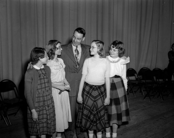 Roger E. Trafford, principal at West junior high school, stands in an auditorium with his students who won the first four places in the school spelling bee. His students, left to right, are Gretchen Idhe, fourth place; Diana DeLess, third place; Virginia Wallace, runner-up; and champion Carol Jane Beery.