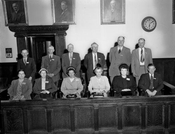 "Group portrait of the George ""Butch"" King murder trial jury.  King, accused of the murder of Sadie Jackson, was declared not guilty by reason of insanity after a 21 day trial.  Left to right, front row: Mrs. Kenneth (Eugenie) Hoover, 64 Lansing Street; Mrs. Percy Olson, Dunkirk; Mrs. Lloyd Kelch, Paoli; Mrs. Fern Fowler, 3315 Blackhawk Drive; Mrs. Irving (Violet) Johnson 2561 Upham Street; and Carl Schwebs, Windsor. Back row: Hubert Kelter, Black Earth; Paul Jensen, Morrisonville; Sidney F. Pollard, 508 Ingersoll, Street; Oscar Hippe, Albion; John Spahn, Sun Prairie; and Einer Johnson, Brooklyn."