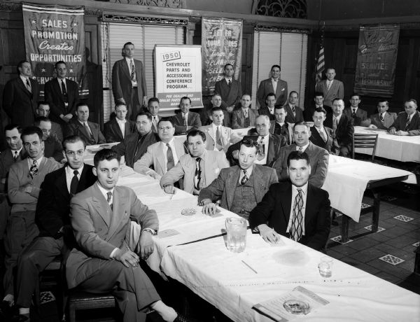Group portrait of men dressed in business suits at a Chevrolet sales meeting.