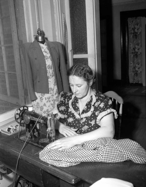 World War II war relief services.  Woman using sewing machine.
