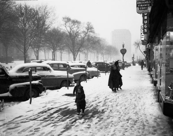 Winter scene with a man and two children navigating the snowy sidewalk on East Main Street on the Capitol Square after a winter storm that dropped eight inches of snow on the city.