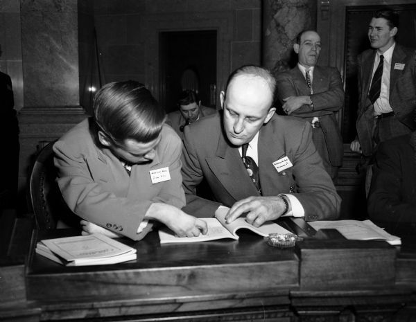 "Two new Wisconsin State legislators, (from left to right) Arne Wicklund, Democrat, Iron and Vilas Counties; and George Sokolowski, Democrat, Milwaukee; confer at the ""school"" for new legislators."