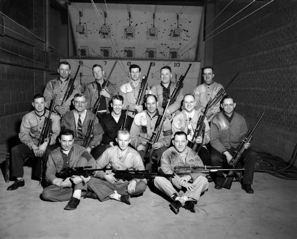 Group portrait of seventeen members of the Madison Rifle club holding their rifles. They repeated as champion of the Southern Wisconsin Rifle League by winning 13 of 15 matches during the recently completed season. Two members of the championship squad are missing from the portrait.