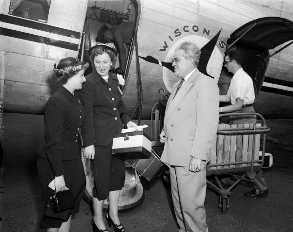 "Bonnie Wainscott (left), age 16, and her mother Mrs. Grace Wainscott are greeted by Francis M. Higgins, President of Wisconsin Central Airlines. The Wainscotts appeared on Tommy Bartlett's ""Welcome Traveler"" program in Chicago and a visit to Madison was arranged through the Wisconsin Central Airlines and the Edgewater Hotel.  Bonnie was stricken with polio when she was 13 months old and Mrs. Higgins was a polio victim in 1907."