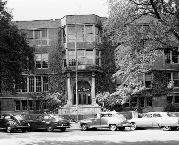 Exterior view of the main entrance to Central High School at Central High School at 214 Wisconsin Avenue.  Four diagonaly parked cars, parking meters, a bicycle, and two shade trees are visible near the school building.