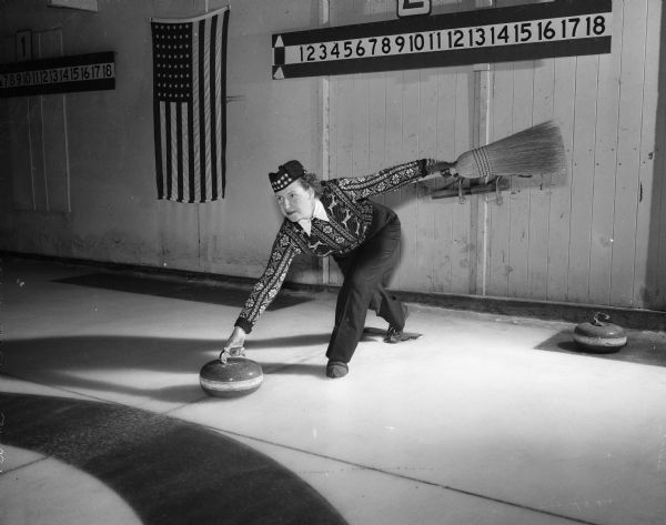 "Esther Onstad releases the ""stone"" on the curling court.  Onstad is a member of the Madison Toories, a women's curling group."