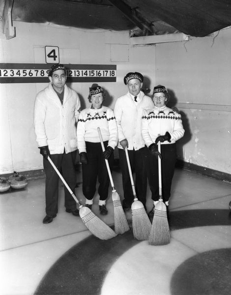 Bud Leonhard, Mrs. Mildred Solheim, Rag Onstad, and Mrs. Esther Onstad, members of the Rag Onstad curling rink of Madison, posing at the second annual mixed bonspiel sponsored by the Portage Curling Club.