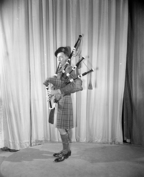 William Chipman, a participant at the University of Wisconsin International Club Costume Ball, wearing an authentic Scottish Royal Stuart costume and playing a bagpipe.