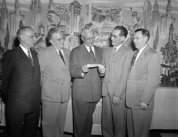 Oscar Rennebohm, president of Rennebohm Drug Stores, Inc., welcoming two new members to the Rennebohm Drug Store 25-year club at the firm's annual pension trust banquet in the Madison club. Rennebohm is presenting checks of $1,250 to the men, Oscar Henning, second from right, pharmacist in charge of pharmaceuticals at the Rennebohm warehouse, and Wilbur Bakke, far right, vice-president in charge of store operations.  Also pictured are George S. Schiefelbein, far left, manager of store No. 2 at 204 State St. (30 years), and Jack Healy, second from left, manager of store No. 3, at 13 W. Main St. (28 years).  Rennebohm has been with the company for 40 years.